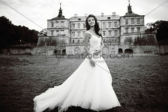 Caucasian young bride next to castle in west Ukraine