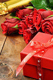 Valentine's setting with red roses, champagne and gift box