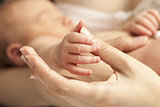 Newborn's hand holding mother's thumb