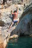 Deep water soloing, rock climber on cliff