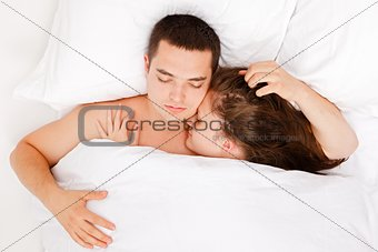 Spouses sleeping in bed