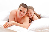 Happy young naked couple in bed