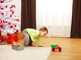 Little boy in Christmas, playing with new toy car