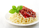 Spaghetti bolognese and green basil leaf