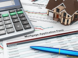 Mortgage application form with a calculator and house.