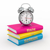 Back to school. Alarm clock on books.