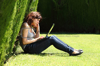 Attractive woman sitting on the grass in a park bored with a laptop
