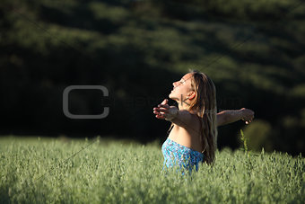 Attractive woman breathing joyful in a green meadow