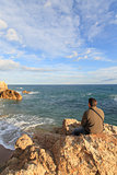 Man sitting on a rock in the beach and looking the sea