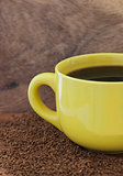 Yellow mug with coffee on the table with a instant coffee granul