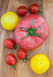 Assorted colorful  wet tomatoes on wooden board