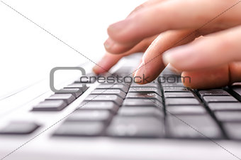 Detail of female fingers typing on keyboard