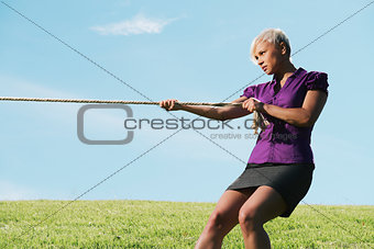 competitive businesswoman playing tug of war with rope