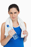 Brunette woman in sportswear with a towel and a bottle