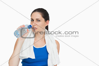 Sportswoman with a towel drinking water