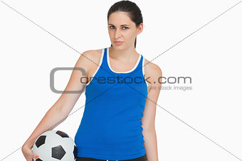 Serious sportswoman with a soccer ball