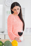 Sad brunette holding a glass of wine