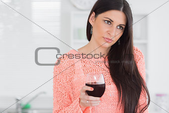 Sad woman holding glass of wine
