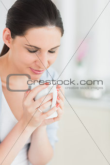 Woman with closed eyes holding a mug