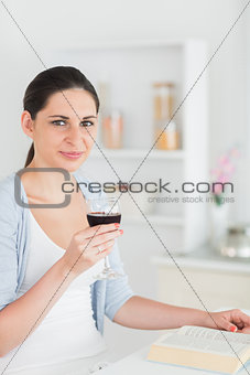 Woman reading and holding red wine glass