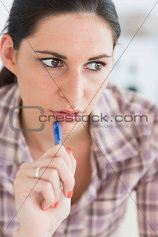 Close up of a woman thinking while holding a pen