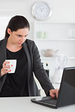 Woman looking at a laptop while holding a mug