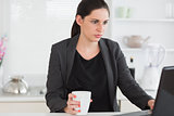 Woman holding a mug while looking at a laptop