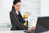 Woman looking at a laptop while holding a juice glass