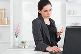 Woman looking at a laptop while holding a milk glass