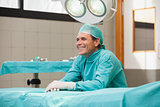 Happy surgeon sitting in operating theatre