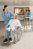 Nurse smiling at old women sitting in wheelchair