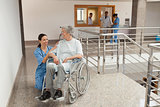 Nurse kneeling beside  old women sitting in wheelchair