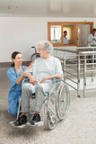 Nurse looking after old women sitting in wheelchair
