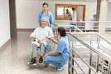 Two nurses looking after old women sitting in wheelchair