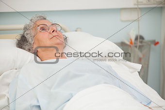 Old woman lying in hospital bed