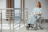 Woman sitting in wheelchair in hospital corridor