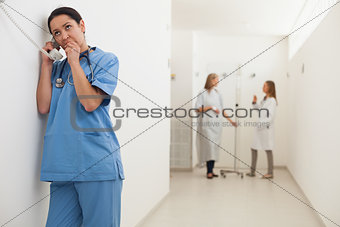 Nurse using payphone with doctor talking to patient