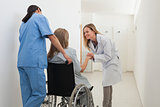 Doctor talking to patient in wheelchair while nurse is pushing