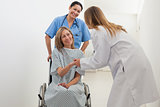 Patient in wheelchair shaking hands with doctor