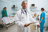 Doctor with folder in busy hospital room