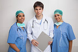 Doctor with clipboard stands between two nurses