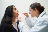 Smiling doctor looking into patient's mouth
