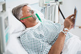 Patient is lying in bed reading in hospital ward