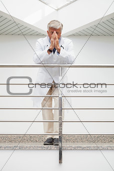 Worried doctor leans against rail