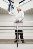 Doctor looking at x-ray leaning against railing