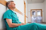 Tired surgeon is sitting on the floor in hospital corridor