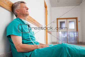 Tired surgeon is sitting on the floor in hospital corridor