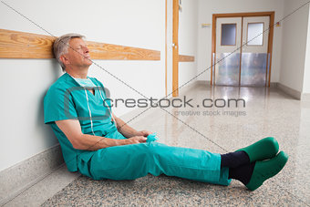 Doctor is sitting on the floor eyes closed