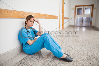 Nurse sitting on the floor hand on forehead