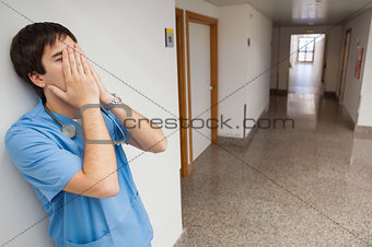 Nurse with hands on face in hospital corridor